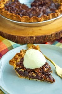 Finished chocolate pecan pie and a slice on a white plate.