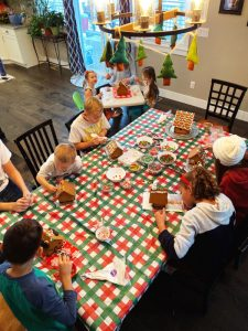 An overhead picture of cousins making gingerbread houses.