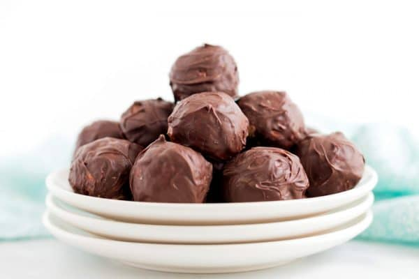 A plate of stacked chocolate peanut butter bon bons.