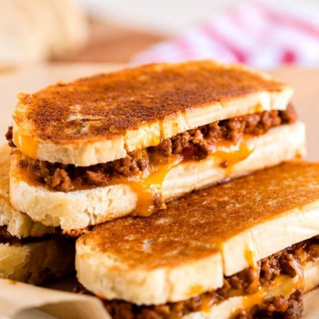 Grilled cheese sloppy joes stacked on a wooden cutting board.