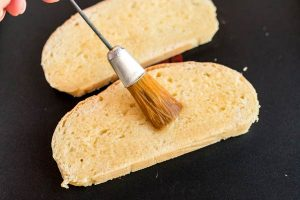Brush the bread with melted butter.