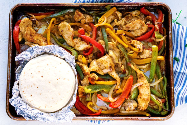 Overhead picture of finished sheet pan fajitas made with chicken.