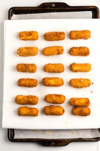 Place the fried cheese sticks on a paper towel-lined baking sheet to drain.
