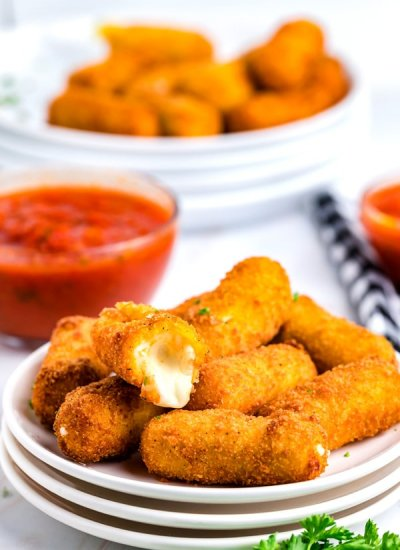 A pile of Mozzarella Cheese Sticks on a white plate with marinara sauce in the background.