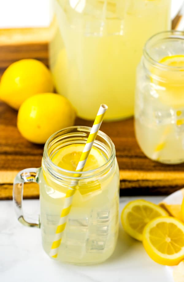 Homemade lemonade in a large pitcher and 2 mason jar cups.