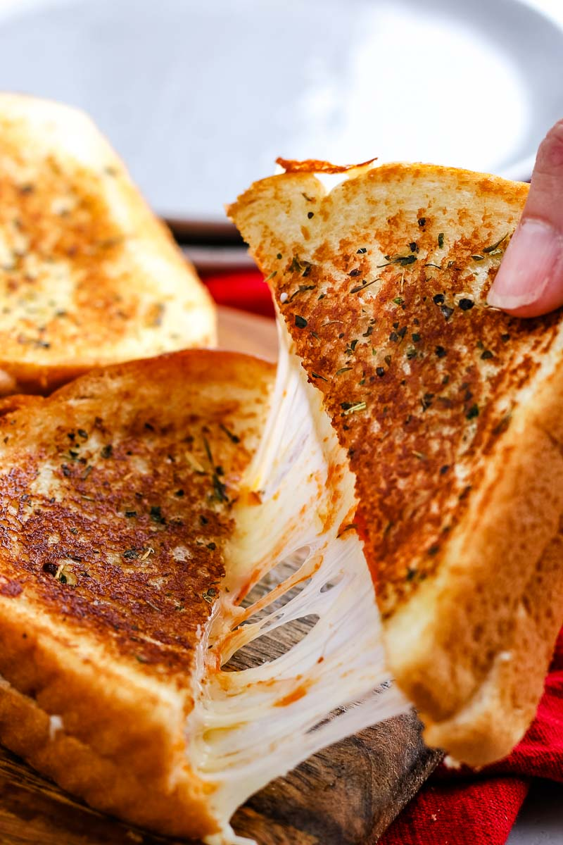 A Pizza Grilled Cheese cut in half and being pulled apart.