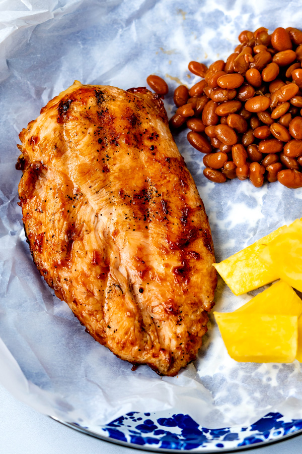 Grilled BBQ Chicken Breast on a blue plate with baked beans and fresh pineapple.