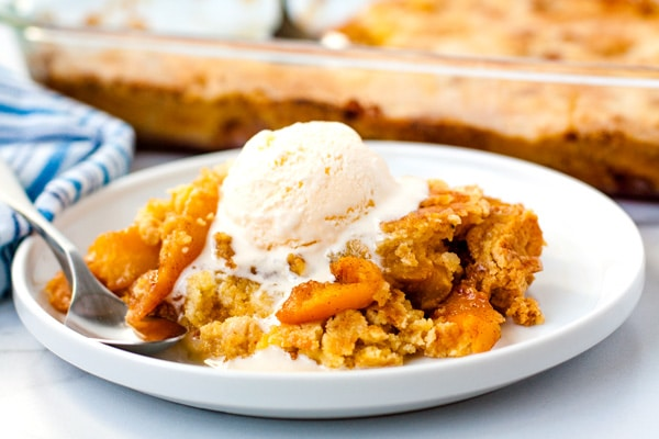 Close up picture of the finished cake mix peach cobbler on a white plate.