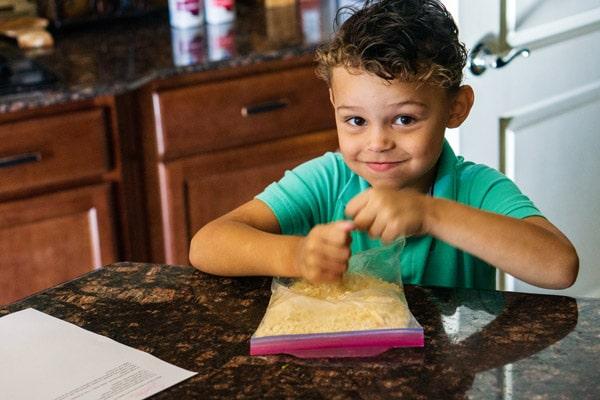 A little boy crushing up crackers in a Ziplock bag.