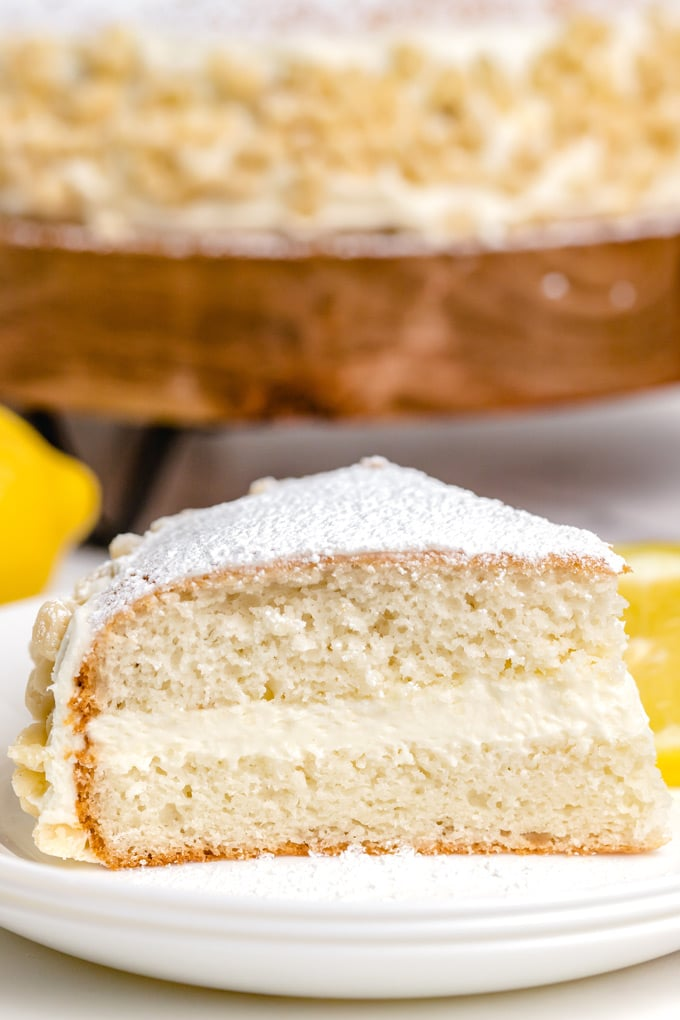 A close up picture of a slice of lemon cream cake on a white plate.