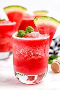 Watermelon smoothie poured into a gladdest and garnished with 2 mint leaves.