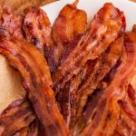 A close up picture of candied bacon strips piled on top of each other.