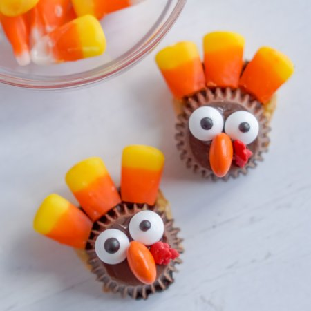 Two turkey Treats on a white surface with candy corns in the background.