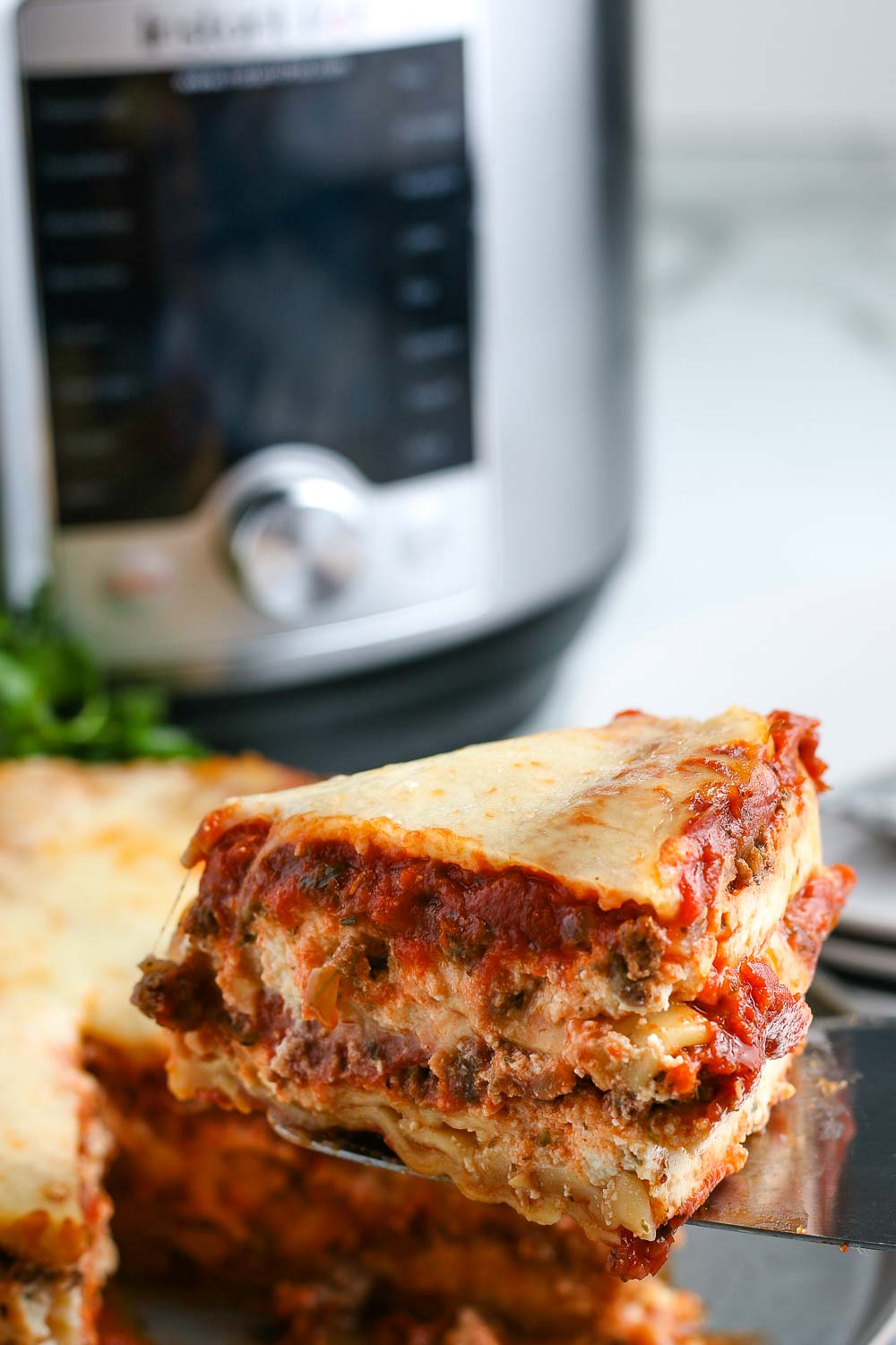 A slice of lasagna being taken out of the finished Instant Pot Lasagna.