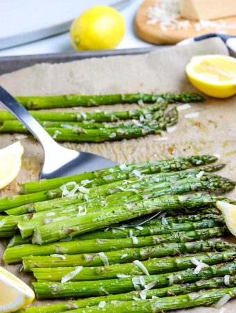 A spatula picking up some roasted asparagus.