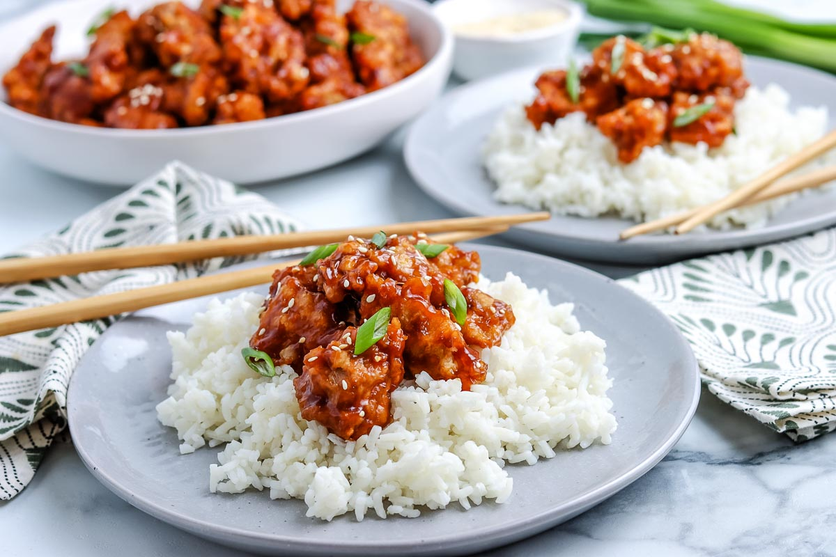 General Tso Chicken on top of white rice on a grey plate.