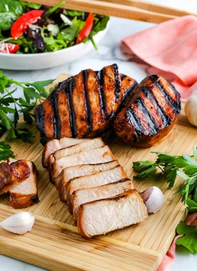 A cooked pork chop cut into slices.