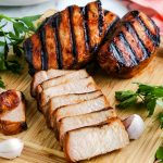 A close up picture of sliced pork chops on a wooden cutting board.