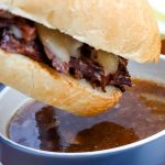 An Instant Pot French Dip being dipped into au jus.
