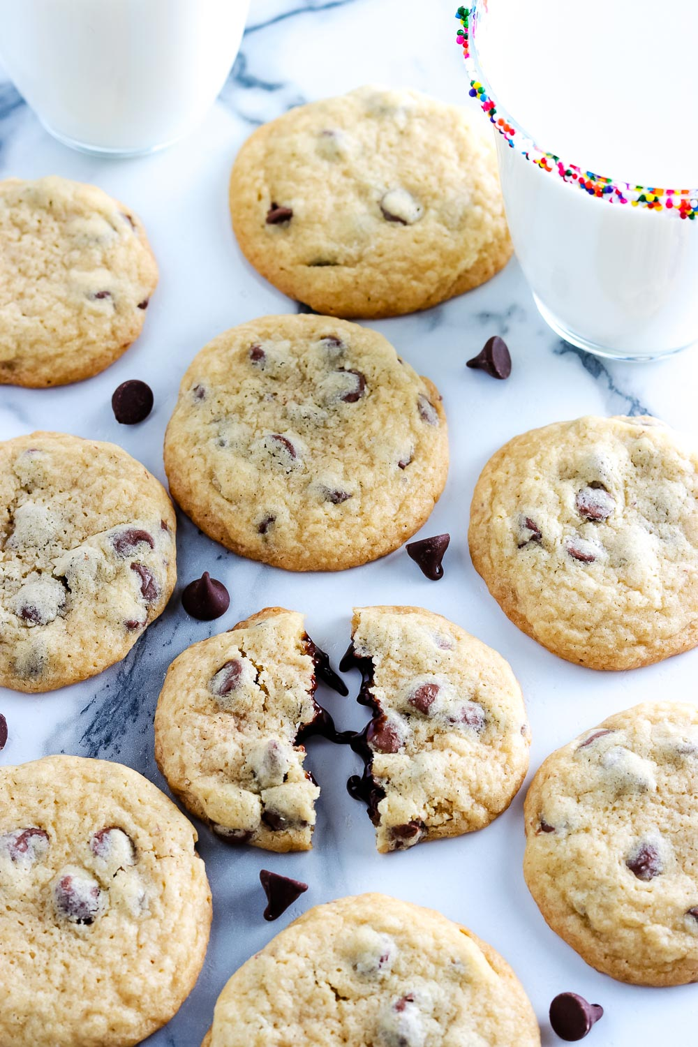 Copycat Mrs. Field's Chocolate Chip Cookies on a marble counter tip with a glass of milk nearby.