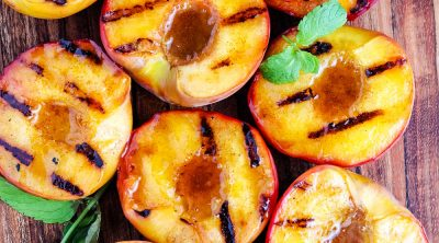 An overhead picture of Grilled Peaches on a wooden cutting board.