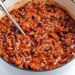 A close up picture of Ground Turkey Chili in a white cast iron pot.