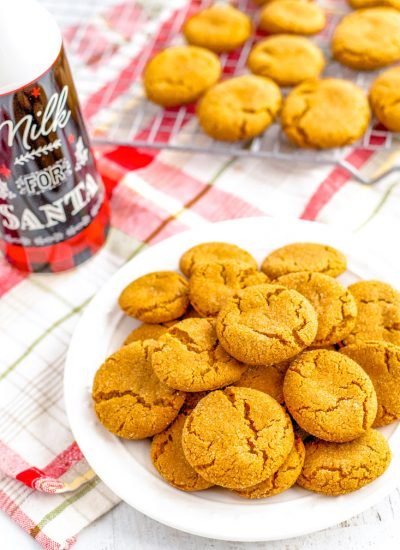 Gingersnap cookies on a plate and some on a wire rack.