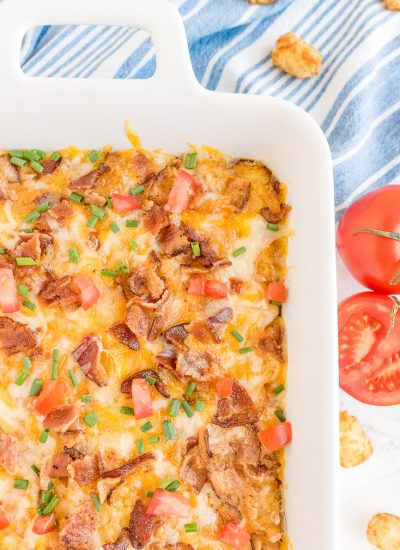 An overhead picture of the finished Tater Tot Breakfast Casserole garnished with tomatoes and green onion.