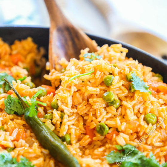 close up of Mexican style rice with peas being scooped onto a spoon