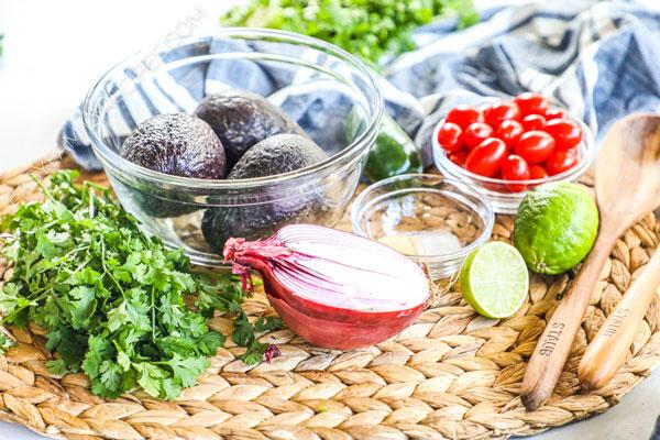Guacamole ingredients including avocado, onion, lime, tomato, cilantro, garlic and salt