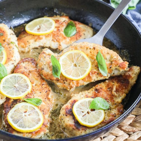 Lifting chicken breast from lemon butter sauce with a spatula