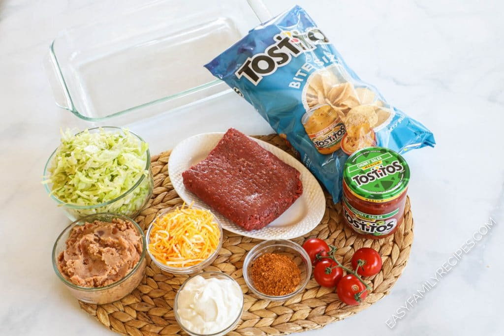Taco Casserole ingredients including - ground beef, beans, cheese, taco seasoning, lettuce, tomato, salsa and chips
