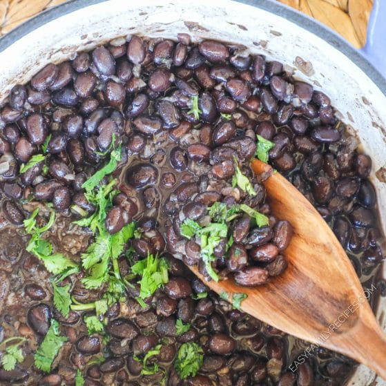 Mexican Canned black beans cooked in a pot and garnished with cilantro