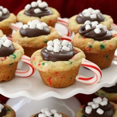 Hot Chocolate Cookie Cups are festive Christmas cookies! Sugar cookie cups filled with fudge, mini marshmallows & sprinkles. Love the candy cane handle! Hot Chocolate Cookie Cups are sugar cookies perfect for the holidays.