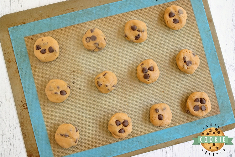 Scooping out butterscotch chocolate chip cookie dough into cookies
