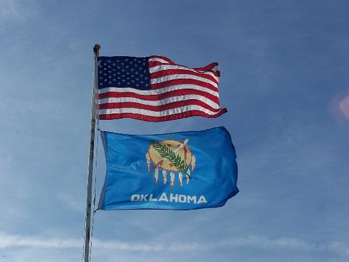 Oklahoma State Flag Beneath The American Flag The