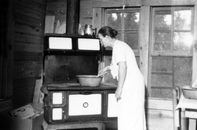 Woman Cooking On A Wood Cook Stove In A House At Delta