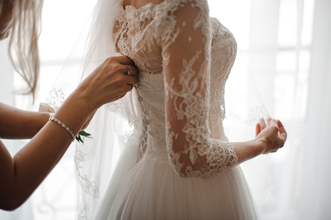how-to-choose-a-bridal-gown-fashionable-bride-getting-gown-zipped-up