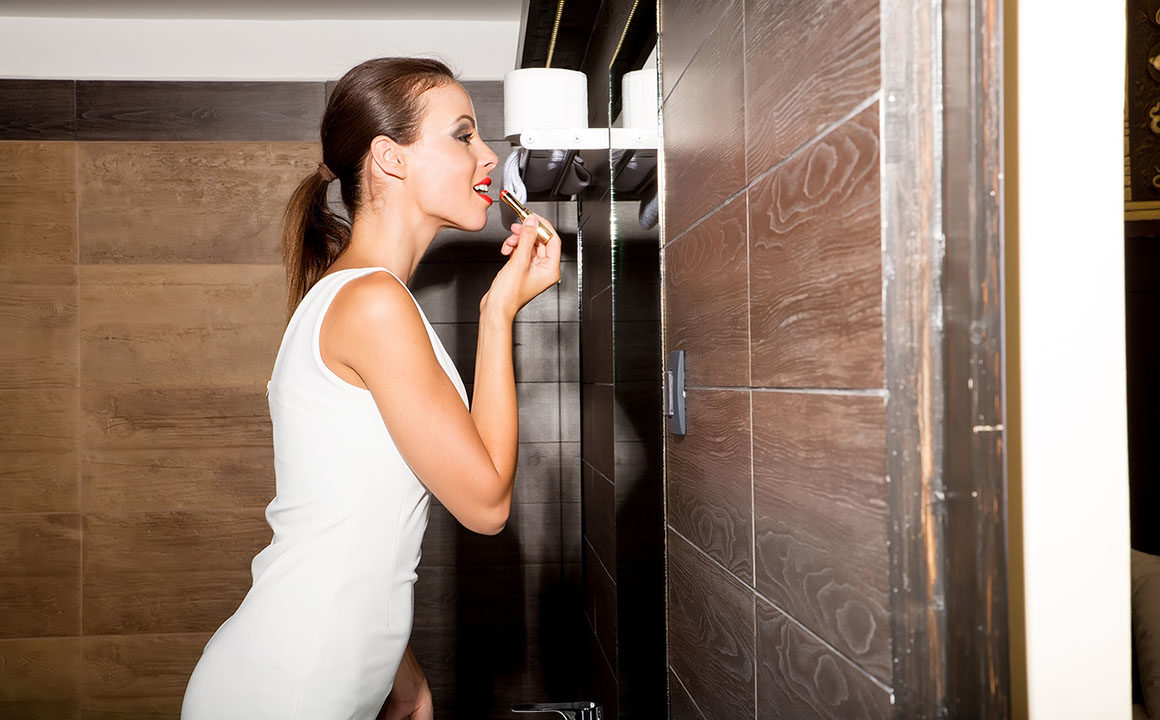 A beautiful young woman putting on makeup in the bathroom and getting ready to go out.