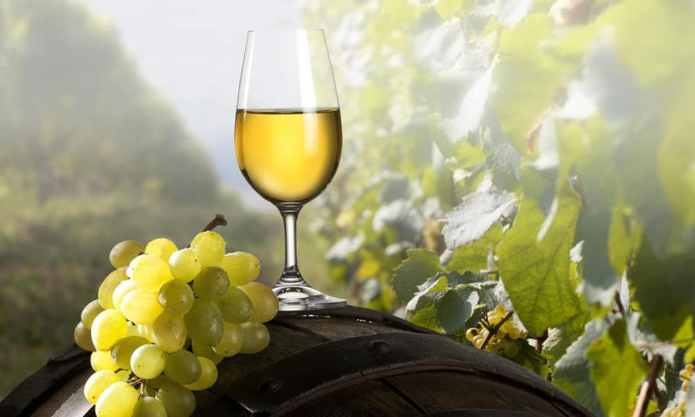 wine-glass-sitting-outside-on-a-barrell-with-grapes