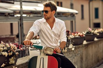 Stylish italian man wearing white shirt and sitting on classic s