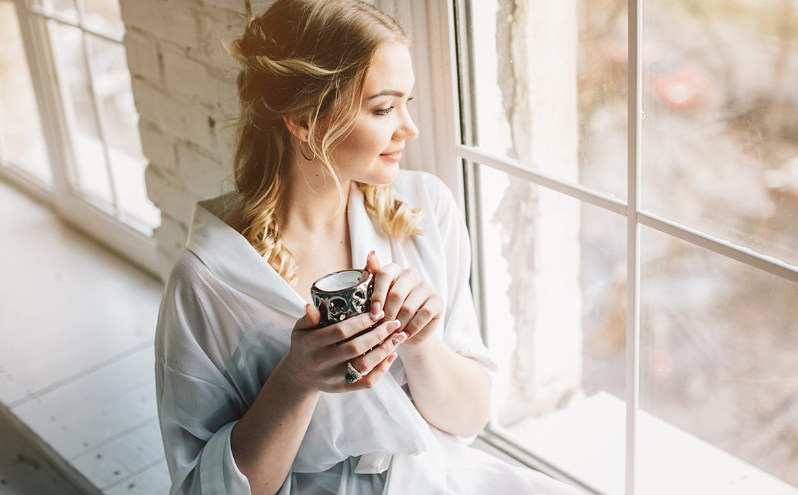 sheer-fashion-trend-woman-in-sheer-looking-out-the-window-drinking-coffee
