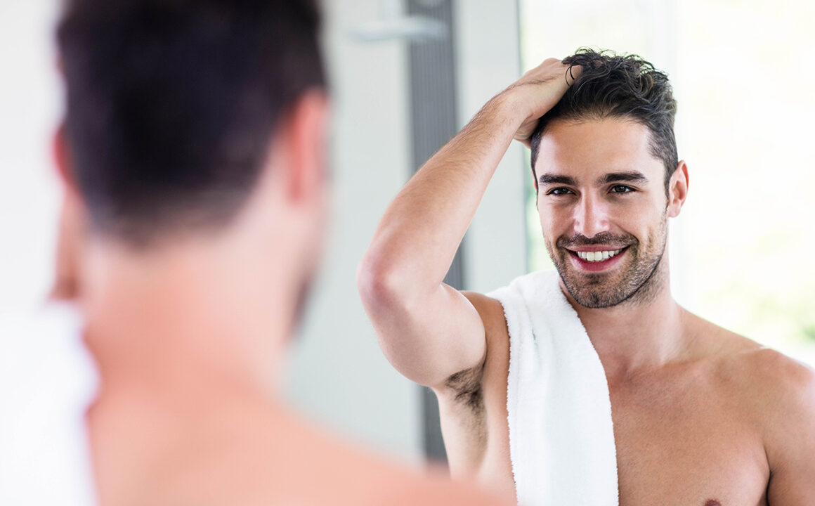 self-care-tips-for-men-man-grooming-his-beard-smiling