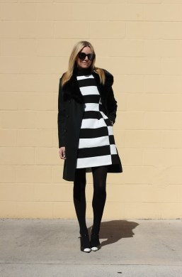 16 Ways To Wear A Striped Dress 2018   FashionTasty com Here we see a black white striped fit and flare frock worn underneath black  tailored coat with fur collar  Complete this outfit by adding big  sunglasses