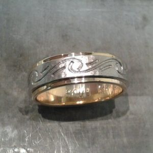 custom wedding band with yellow and white gold and swirl engraving