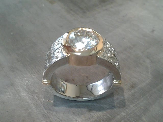 thick 14k gold and white gold engagement band with custom engraving and a round bezel set diamond
