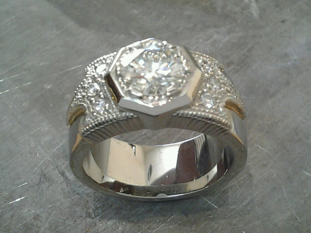 thick white gold band engagement ring with bezel set round diamond and custom engraving along band