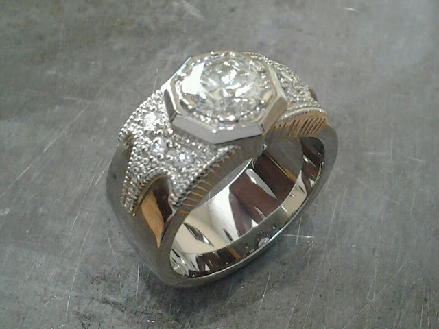 thick white gold band engagement ring with bezel set round diamond and custom engraving along band side view