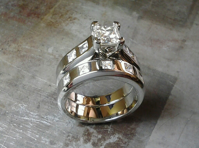 engagement ring and wedding band combo with square cut diamonds flush in the bands and a princess cut diamond in a channel setting