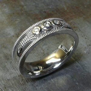 custom wedding band with three round diamonds and engraving